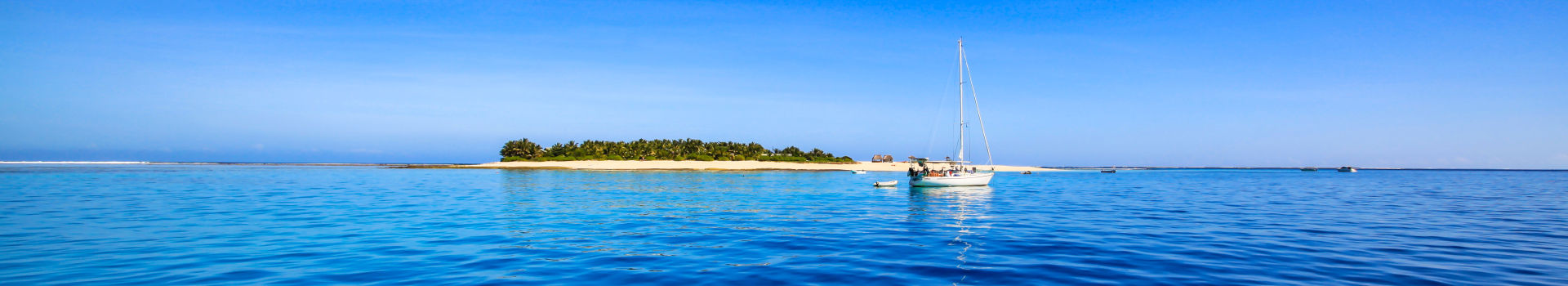 Redseason - Holidays - Boat and beautiful Fiji atoll island with white beach